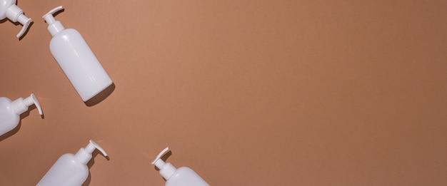 디스펜서가 있는 흰색 병은 갈색 마분지 배경에 놓여 있습니다. 평면도, 평면도. 배너.