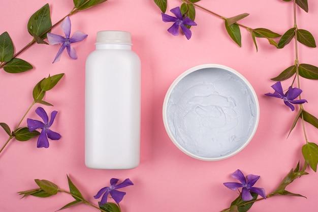 紫の野生の花の上面の枝とピンクの背景にボディ化粧品と白いボトル。