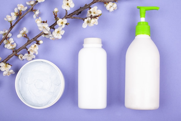 White bottles with body cosmetics on a violet background with white cherry flowers top view close-up.
