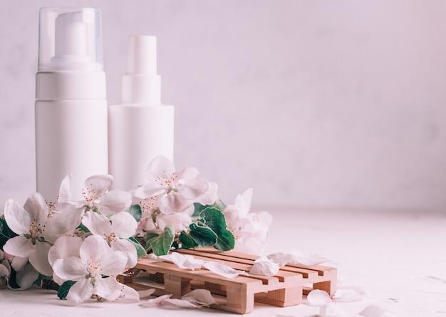 Белые бутылки с косметическими продуктами на деревянном подиуме в виде поддона на светлой штукатурке с цветами яблони. копировать пространство
