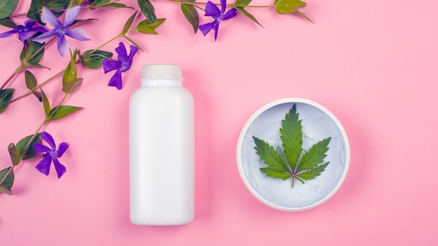White bottles with cosmetics on a pink background with a leaf of marijuana and violet wildflowers top view. beauty, skin care.