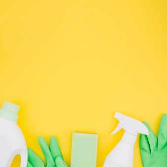 White bottles with green gloves and sponge on yellow backdrop
