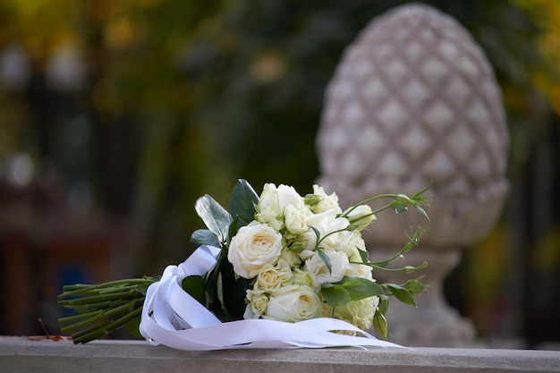 White bouquet of alstroemeria with a white ribbon on a blurred background of a balustrade in the park