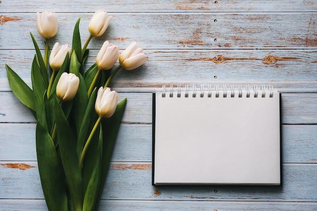 ノートブックと木製のテーブルの上のチューリップの白い花束
