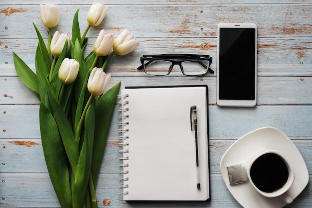 コーヒーカップ、スマートフォン、空のノートブックの木製の背景にチューリップの白い花束