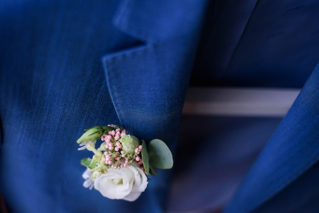 White boutonniere pinned to blue jacket