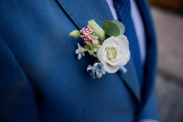 White boutonniere pinned to groom's blue jacket