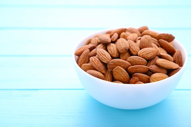 White bowl of almonds on blue background