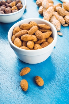 White bowl of almonds; peanuts and peanuts on blue textured backdrop