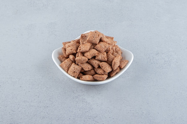 White bowl of chocolate pads cornflakes on stone background. high quality photo