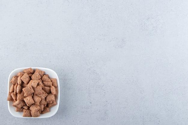 Ciotola bianca di fiocchi di mais in pastiglie di cioccolato sulla superficie della pietra
