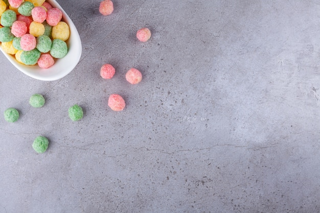 White bowl of colorful cereal balls on stone background.