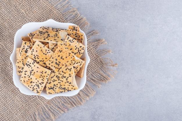 Ciotola bianca di deliziosi cracker croccanti sul tavolo di pietra stone