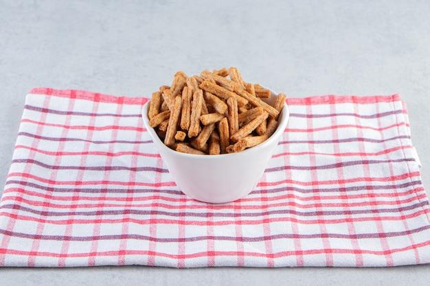 White bowl of crispy stick crackers on stone background.