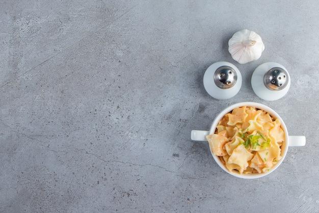 Ciotola bianca di deliziosi maccheroni con aglio e sale su fondo di pietra.