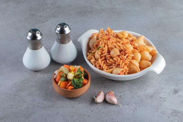 Ciotola bianca di deliziosa pasta e ciotola di insalata di verdure sulla superficie della pietra.