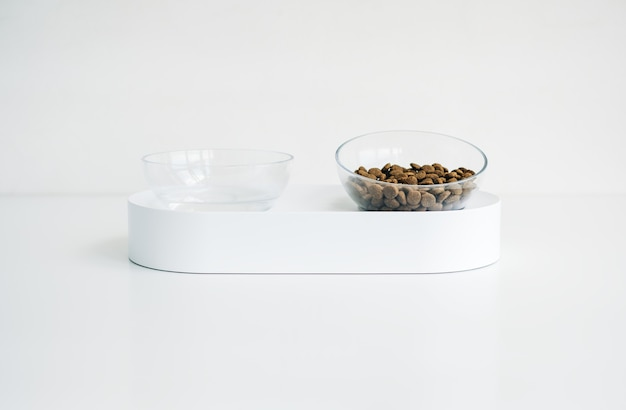 White bowl for dog or cat with feed and water isolated on white background.