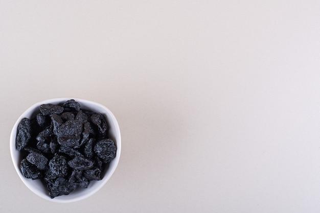 Ciotola bianca di frutta secca di prugne posta su sfondo bianco. foto di alta qualità