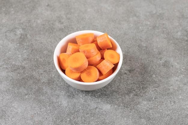 Ciotola bianca di carote fresche a fette sulla superficie di marmo.