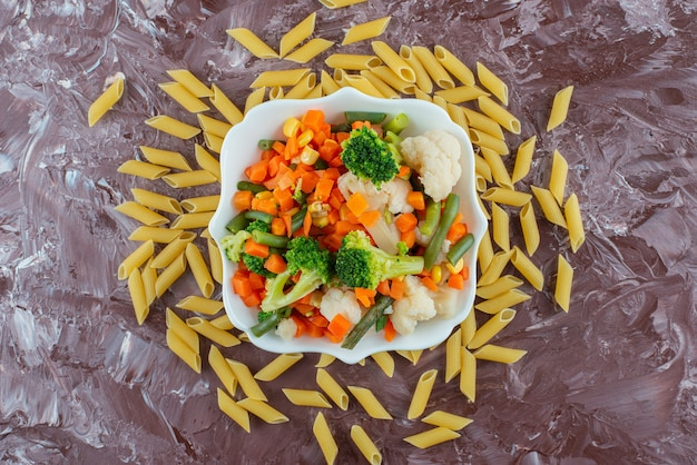 White bowl of fresh vegetables salad and raw penne on marble surface.