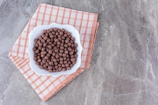 Una ciotola bianca piena di deliziose palline di mais al cioccolato sulla tovaglia.