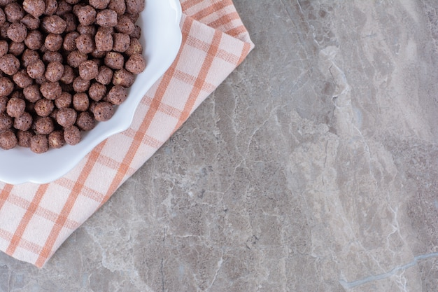 A white bowl full of delicious chocolate corn balls on tablecloth .