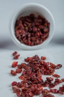 Una ciotola bianca piena di mirtilli rossi secchi.