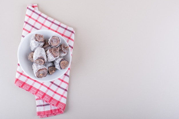 Ciotola bianca piena di cachi secchi su sfondo bianco. foto di alta qualità