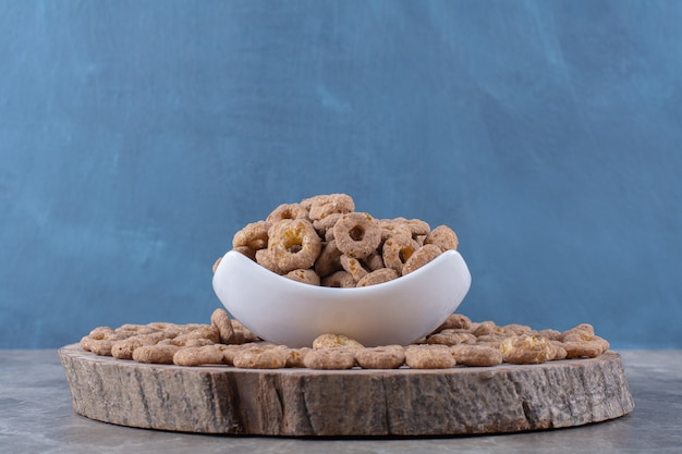 A white bowl full of healthy chocolate cereal rings on a wooden piece .