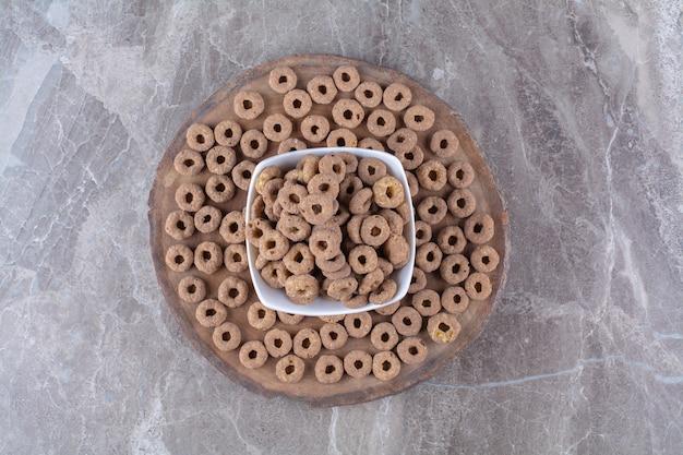 Una ciotola bianca piena di anelli di cereali al cioccolato sani su un pezzo di legno.