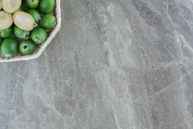 Ciotola bianca piena di succosa feijoa su marmo.