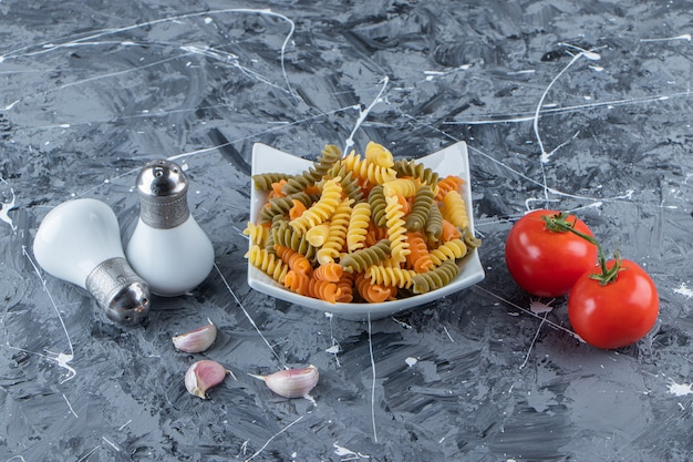 A white bowl full of multi colored macaroni with vegetables and spices on a marble surface .