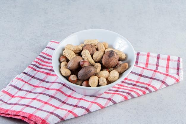 돌 배경에 다양한 껍질을 벗긴 견과류로 가득 찬 흰색 그릇.