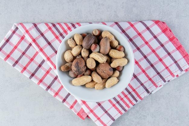石の背景にさまざまな殻付きナッツでいっぱいの白いボウル。
