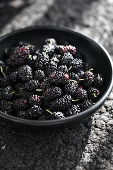 A white bowl full of ripe black mulberries summer fresh mulberry fruit