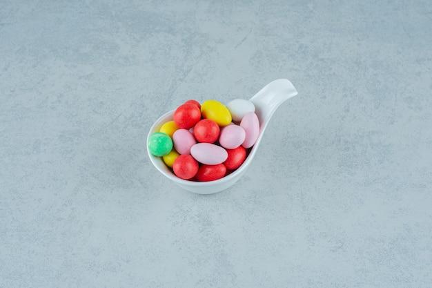 Una ciotola bianca piena di caramelle colorate dolci rotonde su una superficie bianca