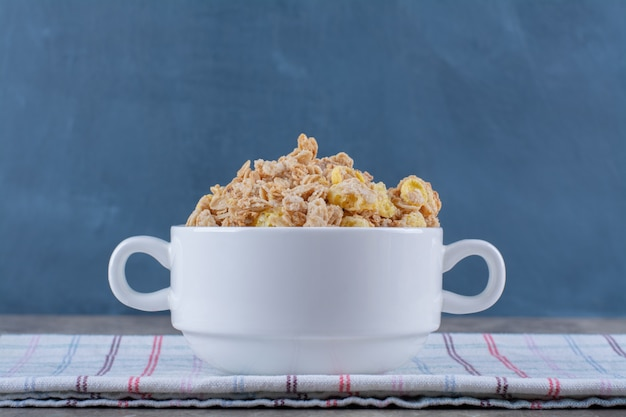 A white bowl full of tasty healthy cornflakes on tablecloth .