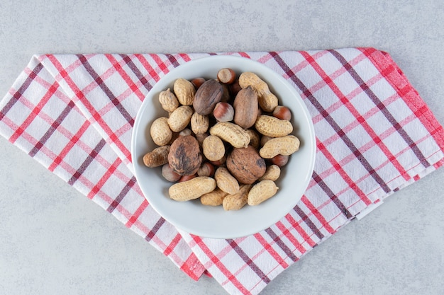 White bowl full of various shelled nuts on stone background.