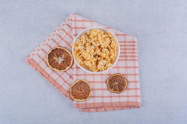 Ciotola bianca di caramelle dure con noci e fette di limone sul tavolo di pietra.