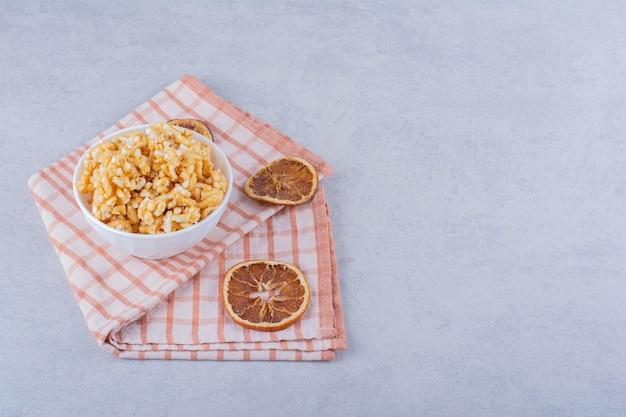 Ciotola bianca di caramelle dure con noci e fette di limone su pietra.