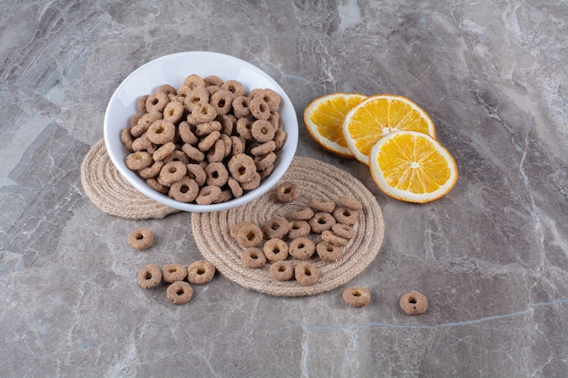 A white bowl of healthy chocolate cereal rings for breakfast .