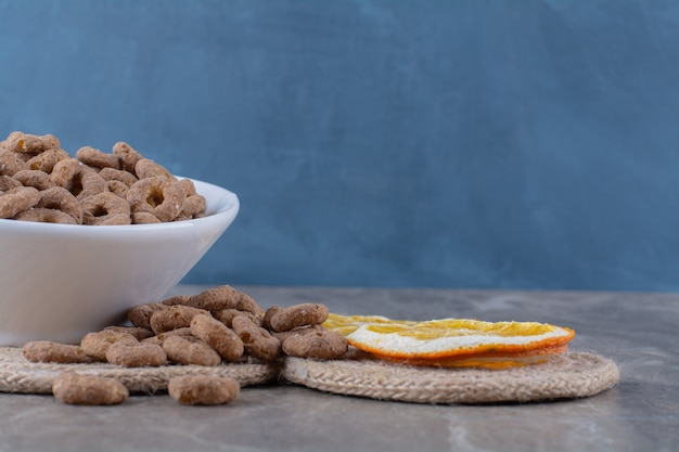 A white bowl of healthy chocolate cereal rings for breakfast