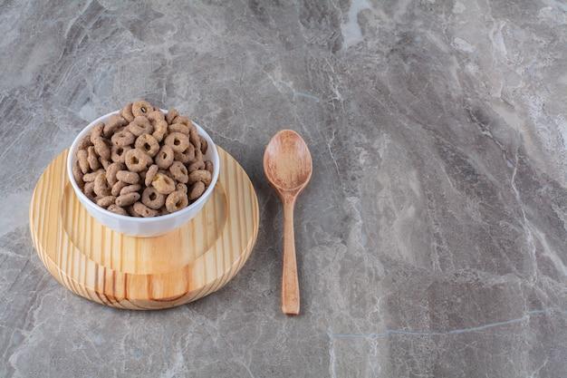 Una ciotola bianca di sani anelli di cereali al cioccolato per colazione