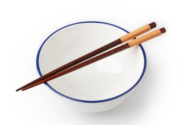 흰색 그릇이 비어 있고 흰색 배경에 격리된 그릇 위에 젓가락이 놓여 있습니다.