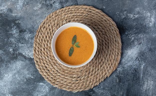 Una ciotola bianca di zuppa di lenticchie su uno sfondo di marmo.