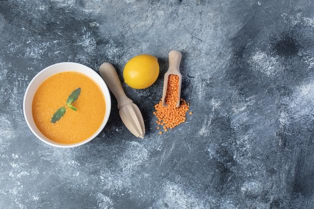 Una ciotola bianca di zuppa di lenticchie con un alesatore di legno.