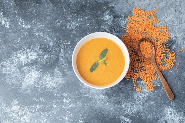 Una ciotola bianca di zuppa di lenticchie con un cucchiaio di legno.