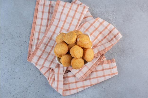 Ciotola bianca di mini torte dolci su fondo di pietra.