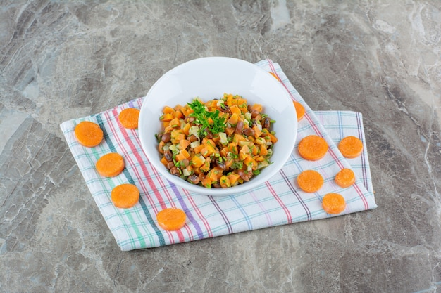 A white bowl of mixed vegetables salad with chopped carrot on a tablecloth .