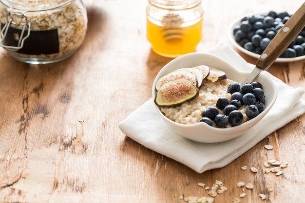 White bowl of oats porridge figs and blueberries.